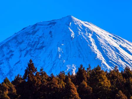 꼭대기가 눈으로 덮인: 푸른 하늘에서 우즈와 아름다운 눈 덮인 후지산 스톡 사진