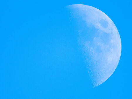 Closeup of right half moon in the silent sky Фото со стока