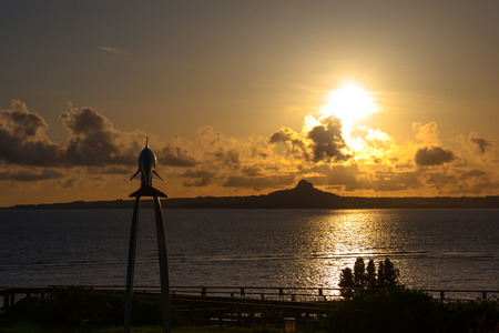 Sunset over the island and dolphin monument photo