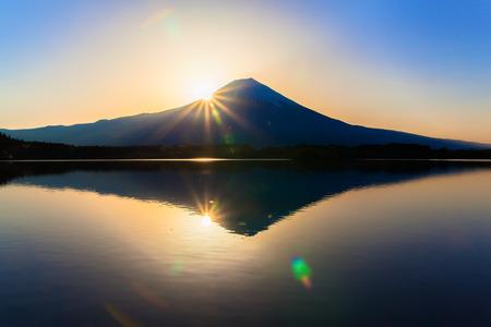 Sun shine and inverted Mount Fuji reflected in Lake Tanukiko 免版税图像 - 31718358