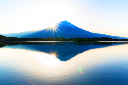Sun shine and inverted Mount Fuji reflected in Lake Tanukiko