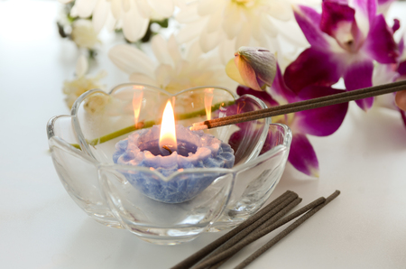 candle and incense sticks with flowers