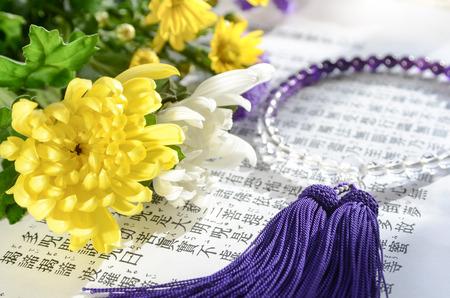 Blumen und Rosenkranz für Buddhismus beten auf Herz Sutra Standard-Bild - 51739761