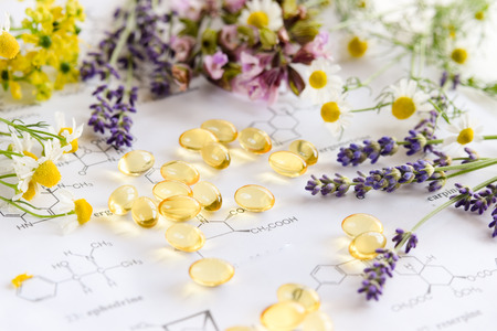 capsules with herbs on science sheet Standard-Bild