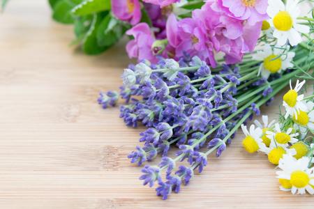 fresh herbal flowers on wooden board