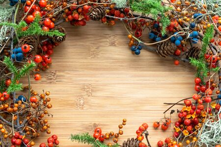 frame of wild plants and berries on wooden board