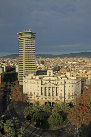 building sector: BARCELONA, SPAIN - DECEMBER 12, 2011: Columbus tower the highest 110 meters construction in the center of Barcelona and Sector Naval de Catalunya - government building. View from Columbus monument
