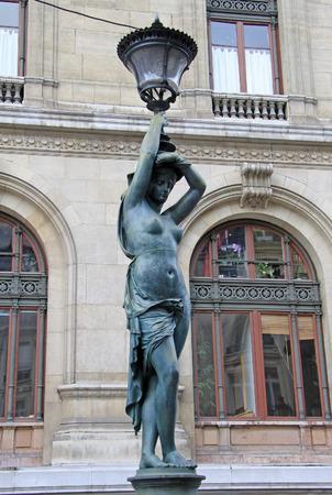 palais garnier: Bronze lamppost shaped as antique caryatide near Palais Garnier, the Paris Opera House in Paris, France Stock Photo