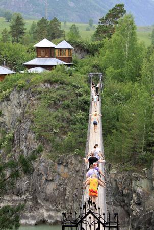 chemal: ALTAI, RUSSIA - JUNE 11, 2012: Suspension bridge to the monastery on the island of Patmos, Altai, Russia
