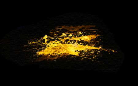 Grunge gold splash isolated on a black background. Texture shape for design. Abstract art drawing. Handwork