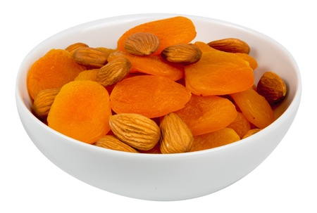 Mixed almonds and dried apricots isolated on white