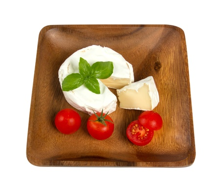 Wooden plate with white cheese and fresh cherry tomatoes closeup