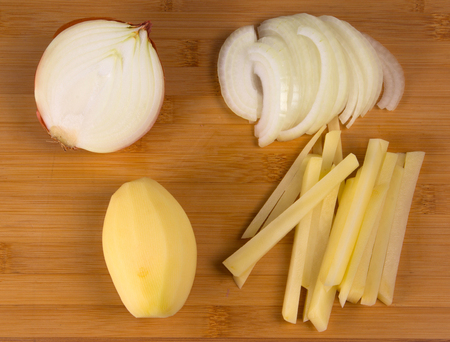 making potato chips - peeling and partially cut potatoes and onions on wooden chopping board