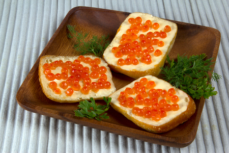 Three sandwiches with red caviar on wooden plate  on white background