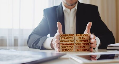 consulting concept. man stacks wooden blocks with inscriptions analysis, strategy, plan, knowledge, teamwork, solution, expertise