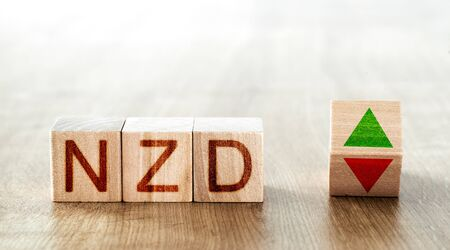 wooden blocks with the inscription nzd and a block symbolizing the rise and fall of financial markets