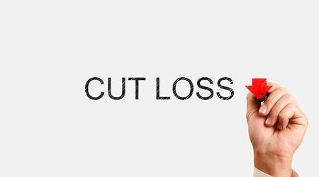Cut Loss concept. male hand writes marker with the words Cut Loss and draws a down arrow