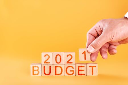 budget 2021 concept. male hand stacks wooden blocks with the inscription budget 2021