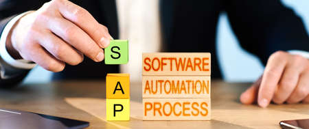 SAP concept. a man collects wooden blocks into the inscription Business process automation software and management software