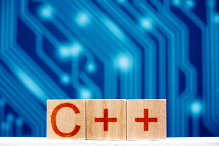 c ++ concept. wooden blocks with c ++ inscription on a blue background with circuit board tracks 版權商用圖片