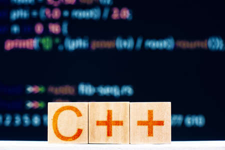 c ++ concept. wooden blocks with the inscription C ++ and program code on the background 版權商用圖片