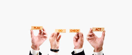 plan do check act. hands hold wooden blocks with plan do check act inscriptions on white background. pdca concept