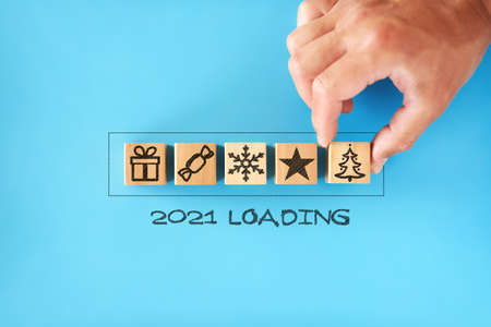2021 loading. man stack wooden cubes with Christmas symbols - tree, gift, snowflake, in progress bar