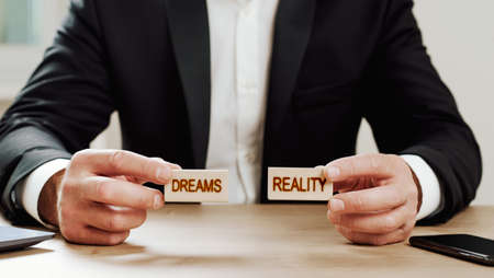 a man holds two wooden blocks in his hands with the words dreams and reality Фото со стока