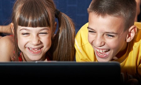 Boy and girl (7-10) using laptop photo