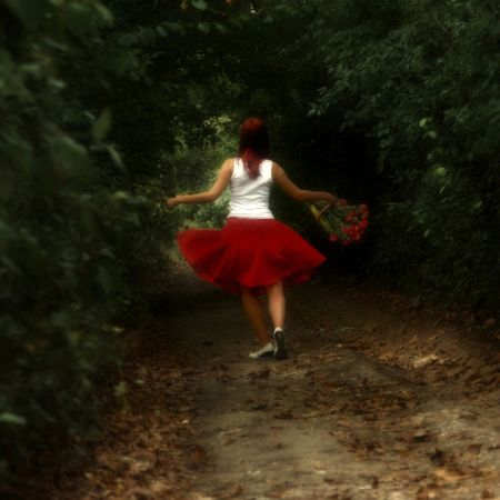 Girl in red dress with the flowers in the woods photo