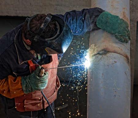 A metalworker welding a metal barrel Stock Photo - 8665541