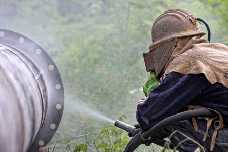 preperation: A worker sandblasting the weld during the construction of pipelines