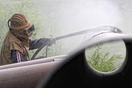Un travailleur sablage au jet de la soudure au cours de la construction de pipelines