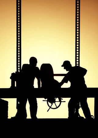 laborers: Silhouettes of workers at work in the evening Stock Photo
