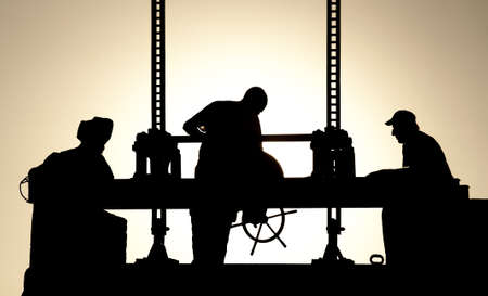 Silhouettes of workers at work in the evening photo