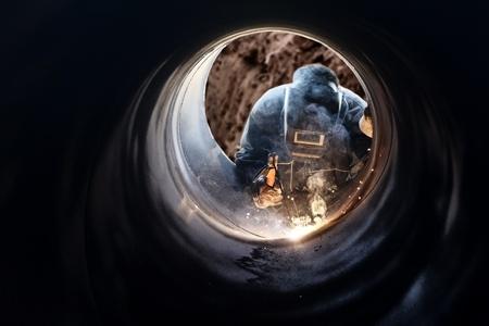 A metalworker welding a metal barrel photo