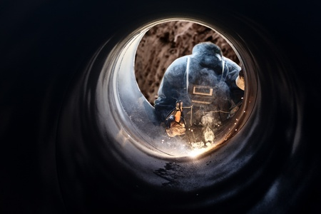 A metalworker welding a metal barrel photo