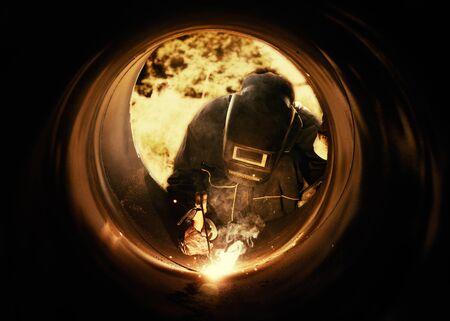 metalworker: A metalworker welding a metal barrel