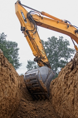 sand pit: Excavator digging a deep trench