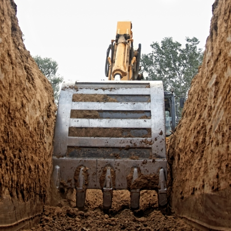 Excavator digging a deep trench photo