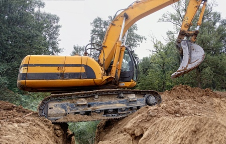 Excavator passes over a deep trench photo