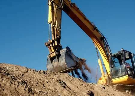Excavator digging the earth with the sky in the background