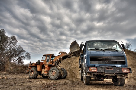 excavator loading gravel into a truck photo