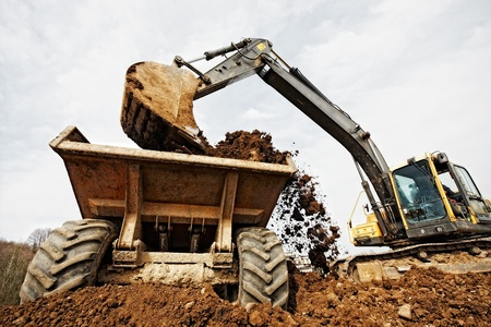 tracked excavator loading the material in a truck Stock Photo