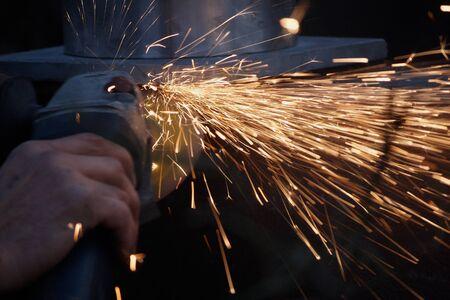 Homme avec un broyeur métallique de meulage, des étincelles