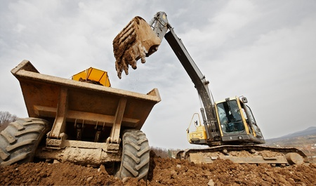 dumps: tracked excavator loading the material in a truck Stock Photo