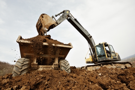 tracked: tracked excavator loading the material in a truck Stock Photo