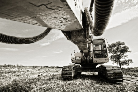 sandpit: Excavator standing in a field ready for work