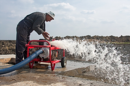 Worker puts into operation the mobile industrial water pump Stock Photo