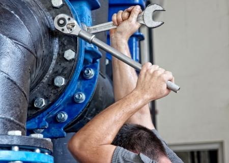 industrial mechanics: hombre aprieta los tornillos, foco en las herramientas Foto de archivo